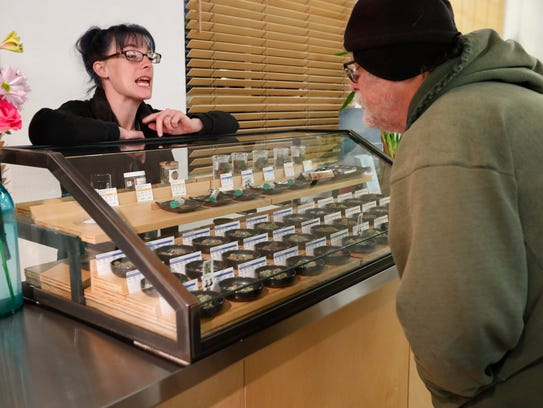 A sales clerk helps a customer with  cannabis samples
