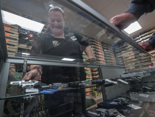 Saleswoman Cathy Lewis shows handguns in a display case to a customer at Second Amendment Sports in Palm Desert on Wednesday, January 3, 2018.