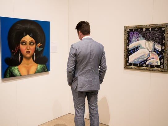 "A man stands between two paintings during the ""Los"