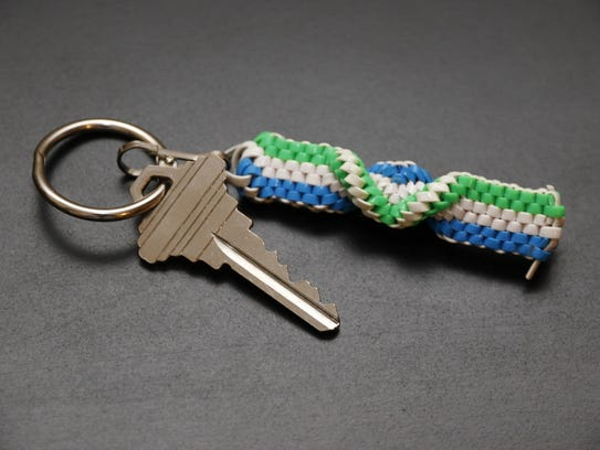 Key on a keychain with a blue, white and green lanyard
