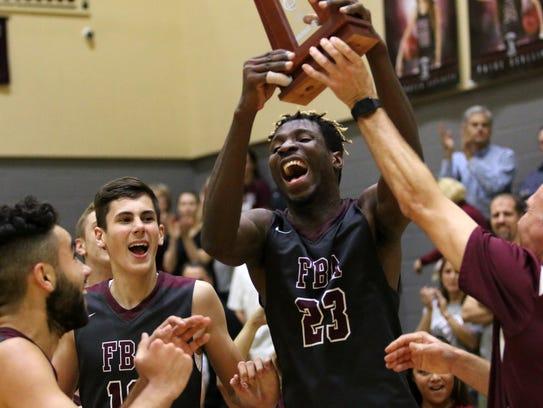 The First Baptist boys basketball team celebrates winning