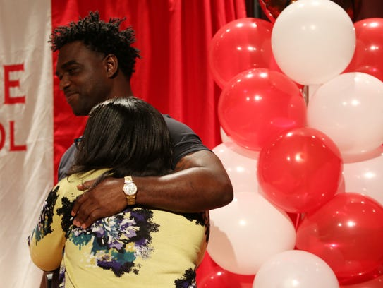 Former Immokalee football player Edgerrin James hugs Immokalee High School assistant principal Rhoderica Washington in the school's auditorium on Wednesday. UnitedHealthcare, along with James and Giants cornerback Dominique Rodgers-Cromartie, presented the school with a $20,000 check to help the athletic department recoup revenue lost to Hurricane Irma.