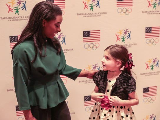 Gold medal Olympian gymnast Simone Biles poses for
