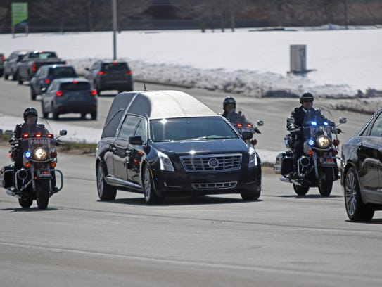 Fellow officers guide the hearse carrying the body