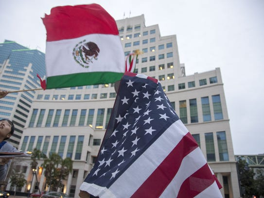 Protesters held U.S. and Mexican flags as they protested against President Trump's immigration policies outside the federal courthouse in San Diego on Tuesday, March 13, 2018.