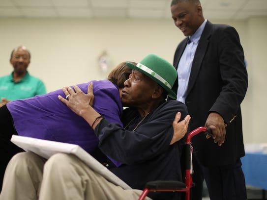 """Ervin """"Mr. J"""" Johnson hugs sky cap Lezlee Carnivale"""
