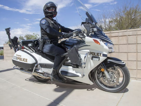 A Tempe motorcycle police officer shows an AR-15 on