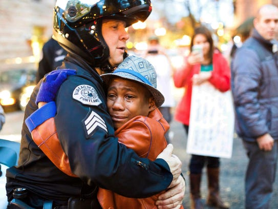 In this Nov. 25, 2014, file photo provided by Johnny Nguyen, Portland police Sgt. Bret Barnum, left, and Devonte Hart, 12, hug at a rally in Portland, Ore., where people had gathered in support of the protests in Ferguson, Mo.