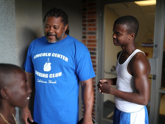 Aziz Ferguson, 15, chats with his trainer Tyres Williams,