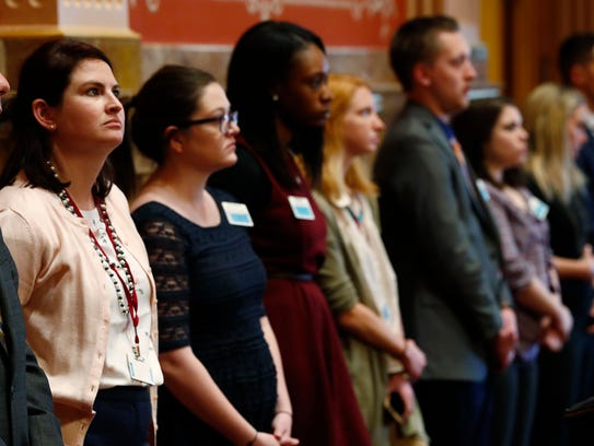 Legislative aides stand in unison during the reading