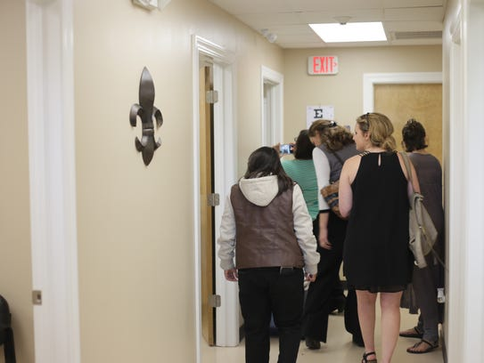 People tour the new school-based clinic at Alexandria