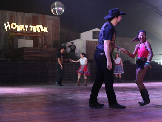 A couple dances in the Honkytonk building at the 2018