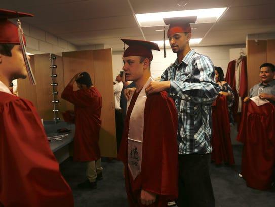 Brad Huffman, right, helps Alex Martin adjust his graduation