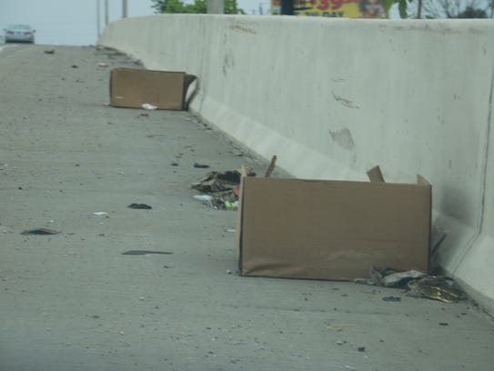 Discarded boxes litter the roadside along I-465 in