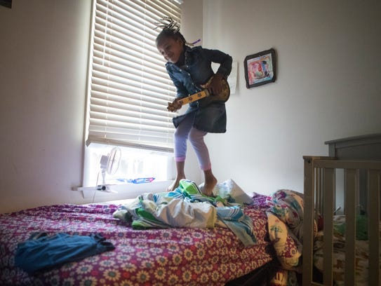 Taralyn Drew, 6, jumps on her bed while playing with