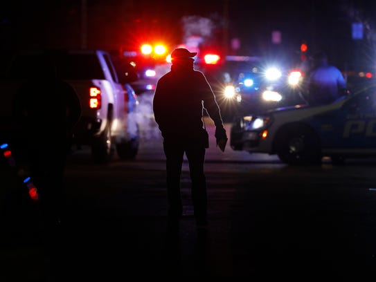Police search the area where a police officer who works