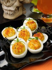Stuffed eggs are designed to look like pumpkins on the holiday table in honor of Halloween.