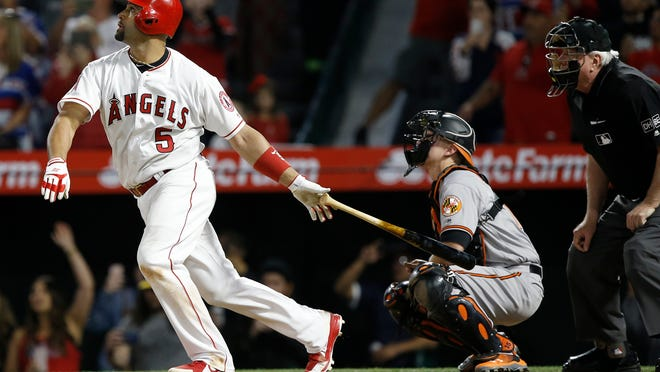 Los Angeles Angels' Albert Pujols, left, watches his fly-out to right field, in front of Baltimore Orioles catcher Chance Sisco, center, and umpire Brian Gorman during the eighth inning of a baseball game in Anaheim, Calif., Thursday, May 3, 2018. The Angels won 12-3. (AP Photo/Alex Gallardo)