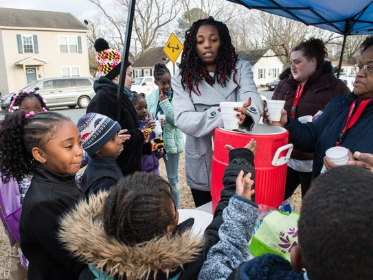 Amber Green, center, distributes hot cocoa and snacks