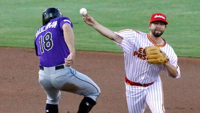 El Paso Chihuahuas short stop Peter Van Gansen throws to first base for a double play attempt as Mike Tauchman of the Albuquerque Isotopes moves out of the way Wednesday night at Southwest University Park.