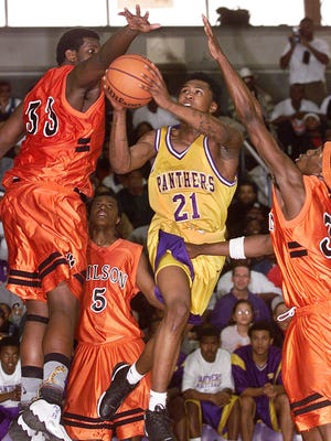 Camden's Dajuan Wagner drives throught Woodrow Wilson players (Ledt to right) #33 Marquis Gantt, #5 Kris Polk, and #34 Sidner Francis in the second Half on March 3, 2001. Photo by Shawn Sullivan