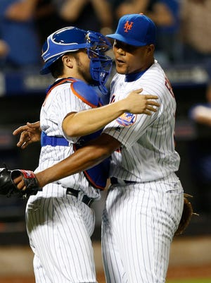 Mets catcher Travis d'Arnaud and Mets relief pitcher Jeurys Familia hug after defeating the Royals 2-1 at Citi Field.