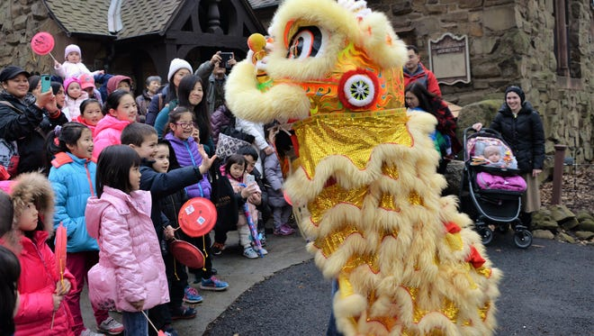 The ceremonial lion does a dance before leading chilldren and their parents on a parade through the Hartshorn Arboretum.