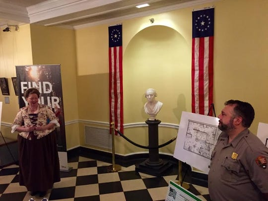 A historical re-enactor speaks about George Washington and Fords Mansion as Morristown National Historical Park superintendent Tom Ross looks on.