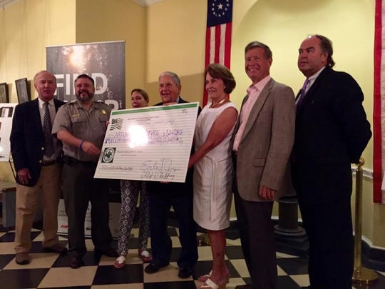Elected officials, members of the Washington Association and members of the National Historic Park hold a $1.3 million check.