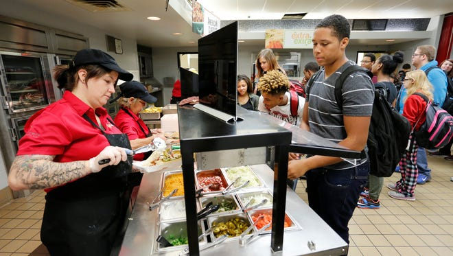 """Roberta Kerfoot, left, serves DeLeon Holmes at the Sono Bar Wednesday, October 12, 2016, in the cafeteria at Lafayette Jeff. The Sono Bar offers Latin foods. """"It's pretty good,"""" said Holmes, a junior. """"It's much better than the old stuff."""""""