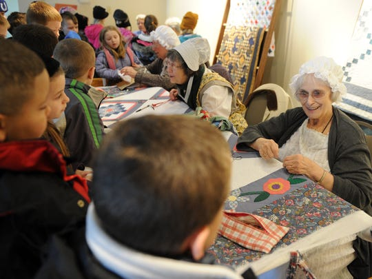 Sharon Yunker, right, explains quilting techniques to students who were visiting a previous Spring Farm Fest at Angel Mounds. The event showcases different aspects of Indiana farming culture through the ages.