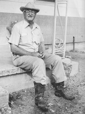 Tom Poteet peels a pecan while waiting for a delivery of steers at Midwest Feedlot in San Angelo in the 1970s.