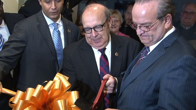 """New Castle County Councilman Bill Bell cuts the ribbon Tuesday on a new """"Fusion Center"""" named in his honor at the Paul J. Sweeney Public Safety Building off U.S. 13, flanked by County Executive Thomas P. Gordon (right) and Chief Administrative Officer David Grimaldi."""