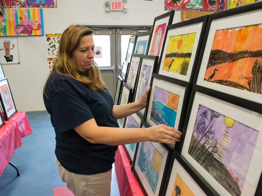Teresa Tyler, Art Teacher at the Wicomico Day School holds a student painting on Wednesday, May 10, 2017.
