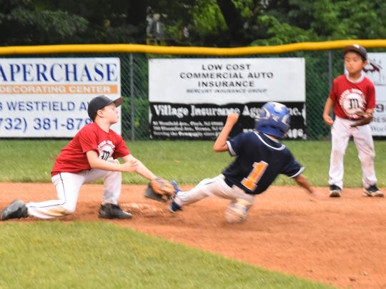 Shortstop Kieran Gerne tagging out Colonia's Coute Scaff from catcher Charlie Wall's throw on an attempted steal of second in the top of the sixth inning in the Clark finals as second baseman Koji Fujita looks on.
