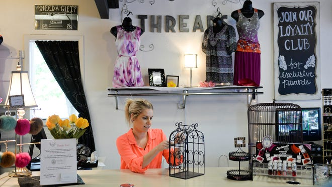 Laura Koford, a sales associate at Threads Boutique, prices a metal cage Wednesday afternoon, June 1, at the store. The store is closing June 4.