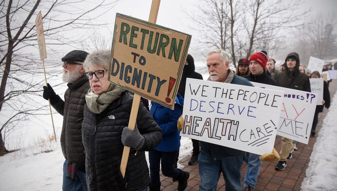 Protesters carry signs while walking along the shores of Lake George Friday, Jan. 20, in St. Cloud. A group of about 40 protesters gathered Friday afternoon in opposition to the policies of President Donald Trump.