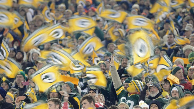 Green Bay Packers fans wave flags during a 2014 game against the Chicago Bears at Lambeau Field.