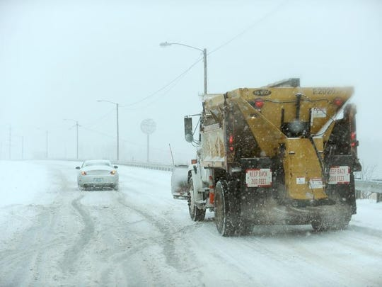 A driver struggles to climb an overpass on Hinkleville Road as a snow plow approaches in Paducah, Ky., on Dec. 6.