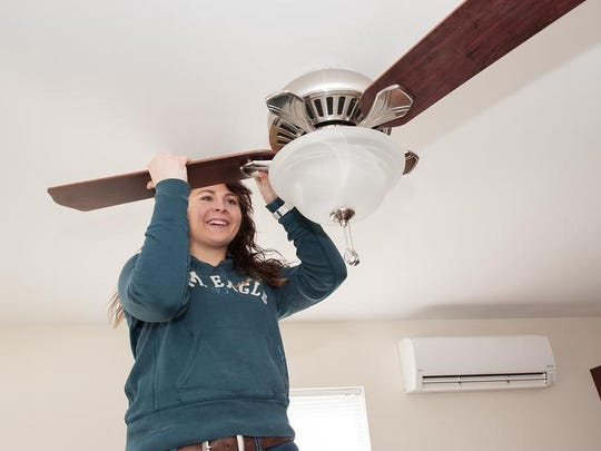 Habitat for Humanity volunteer Danielle Niethammer not only can install a ceiling fan but also hang siding and paint.