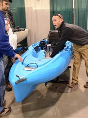 Hobie kayak sales representative Ryan Barkley talks about some of the advantages of the foot pedal-powered kayaks his company sells at the 2015 Ultimate Fishing Show at Novi's Suburban Collection Showplace in this file photo.