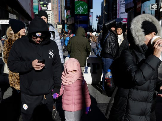 Pedestrians try to keep warm while walking in Times