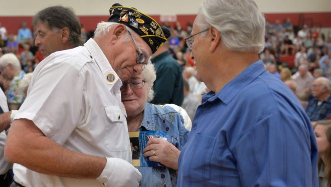 Upsala American Legion Post 350 member Mike Barten hugs Lois Klug and Donald Kalis, the siblings of soldier Gerald Kalis, who died in the Vietnam War. Barton was a medic with Gerald Kalis and held Kalis in his arms when he died.