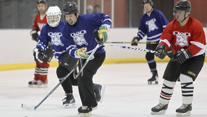 Oshkosh police and fire fighters compete on the ice in a game of hockey for the sixth annual Guns N Hoses charity game at the YMCA in this 2013 file photo.