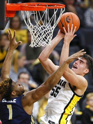Iowa center Luka Garza (55) drives to the basket over Oral Roberts forward Elijah Lufile during a game in Iowa City.
