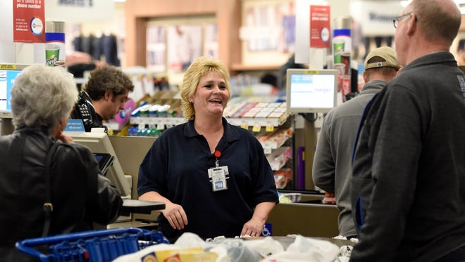 Meijer employee Laura Stofleth laughs with customers Bob and Terri Clement of Henderson while helping them checkout at the store in Evansville Tuesday.  Stofleth has been working at the store since it opened on April 1.