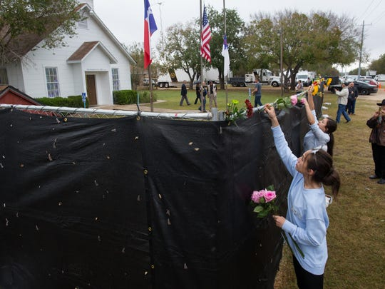 Flowers are placed Sunday, Nov. 12, 2017, on top of the fence surrounding the First Baptist Church of Sutherland Springs. One week earlier a shooting left 25 people and an unborn child dead.
