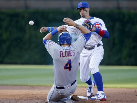Javier Baez makes a throw during a Mets-Cubs game at