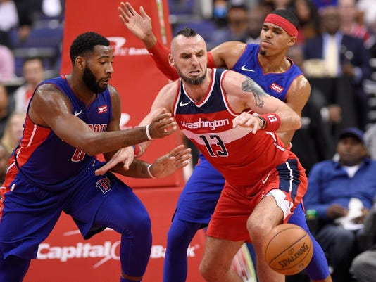 Detroit Pistons center Andre Drummond, left, battles for the ball against Washington Wizards center Marcin Gortat (13), of Poland, during the first half of an NBA basketball game, Friday, Oct. 20, 2017, in Washington. Detroit Pistons forward Tobias Harris is at right rear. (AP Photo/Nick Wass)
