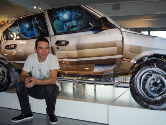 Photographer Cyrill Hatt with a sculpture of  a crashed car made from his photos.